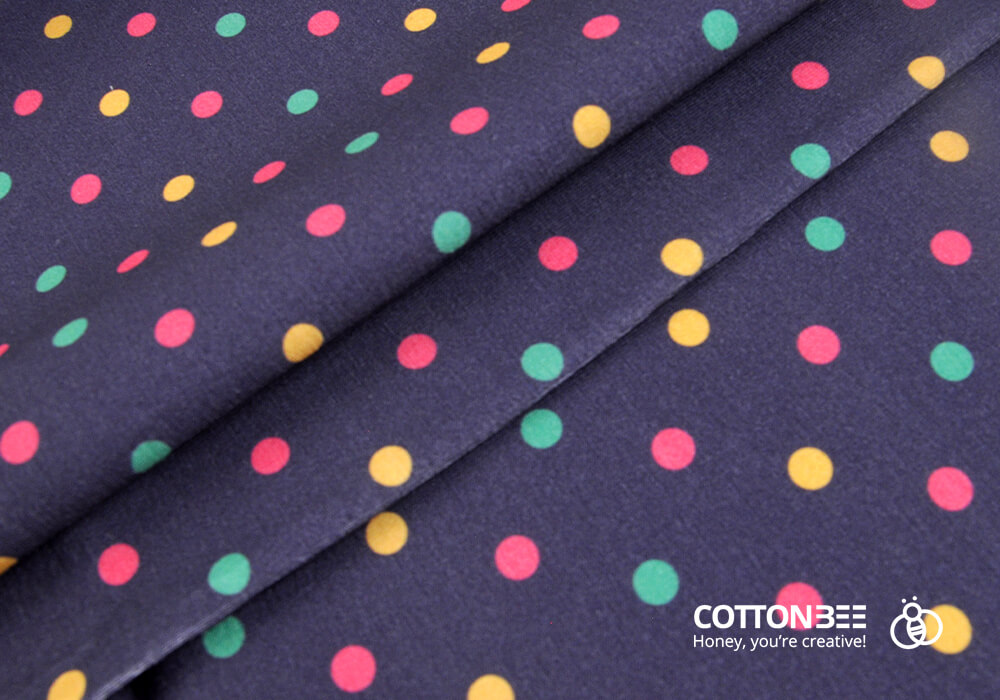 Picture of dark fabric with colourful polka dot print