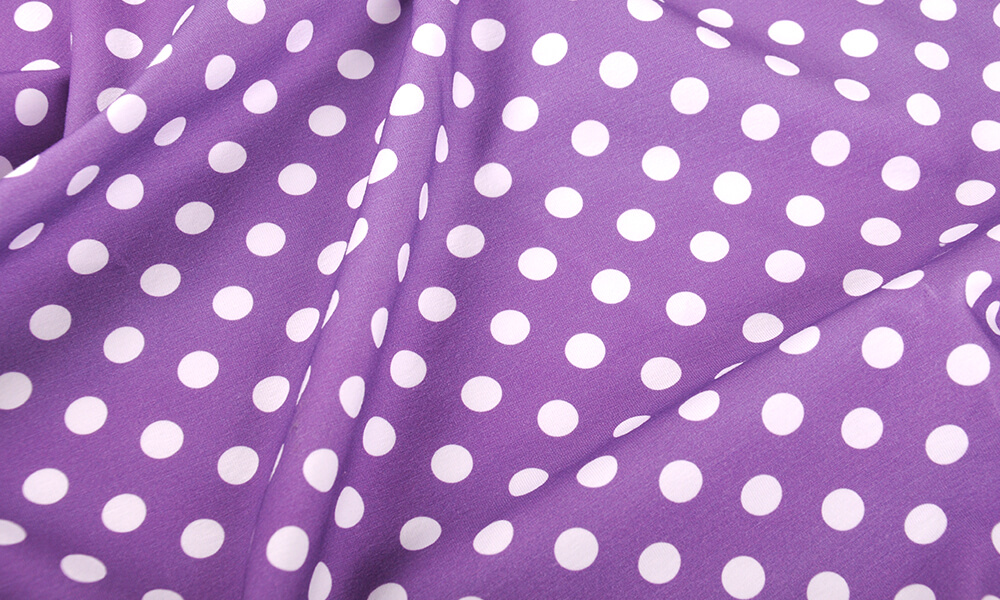 Picture of purple fabric with white polka dot print